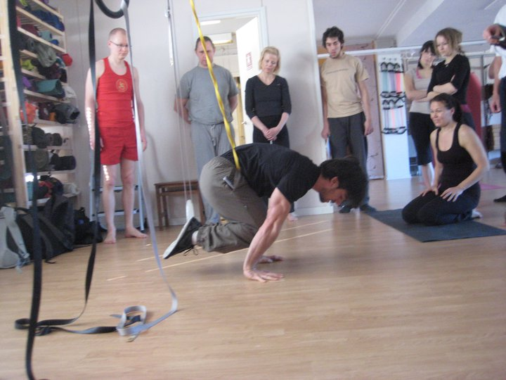 Ido Portal demonstrating how to work on on band-assisted tuck planche.