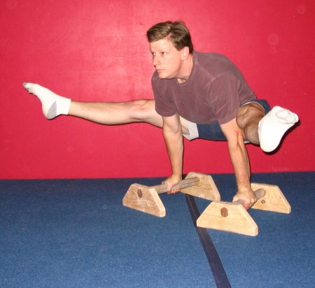 Roger Harrell demonstrating a Straddle L with the knees above the elbows (Very difficult).